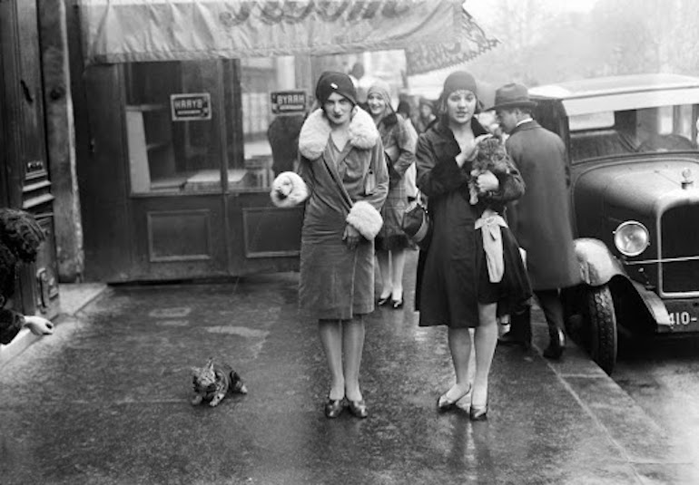 Young women walking their cat in November 1929 in Paris, France.