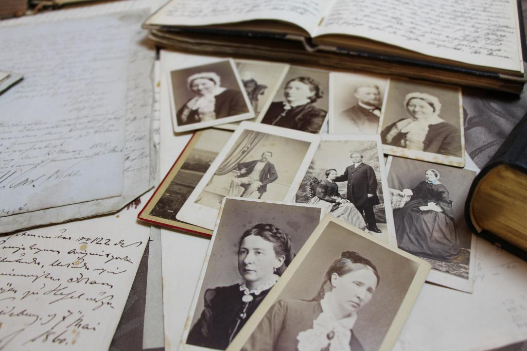 Table with antique photos and handwritten documents.
