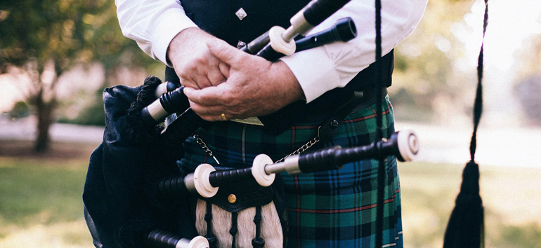 Scottish man wearing a tartan kilt.