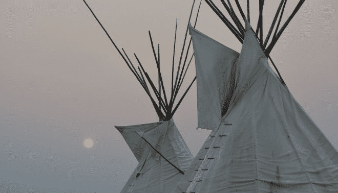 Teepees against a grey sky with low sun.