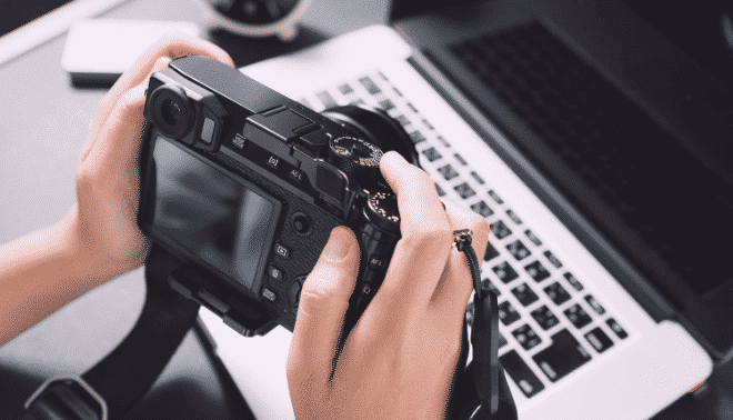Person holding a digital camera next to a laptop.