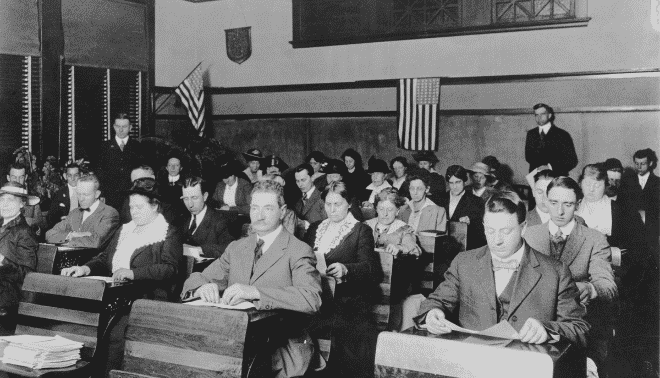 Classroom of immigrants learning English and US political culture in 1920.