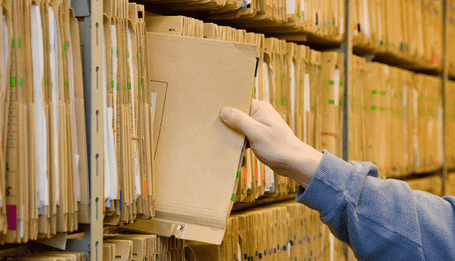 Man pulling a folder out of an archive.
