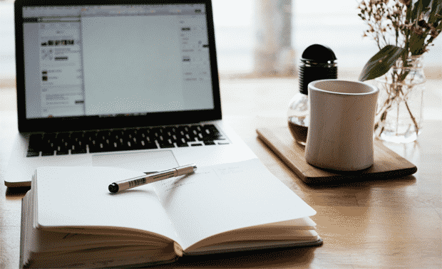 Laptop with notepad and coffee