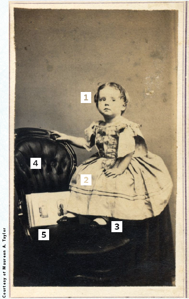 Civil war-era portrait of a young girl posing with a family album.
