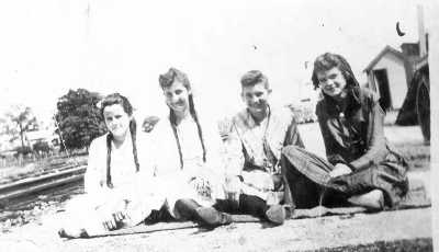 The dresses on the four girls sitting near the railroad tracks in this candid snapshot date it to about 1900.