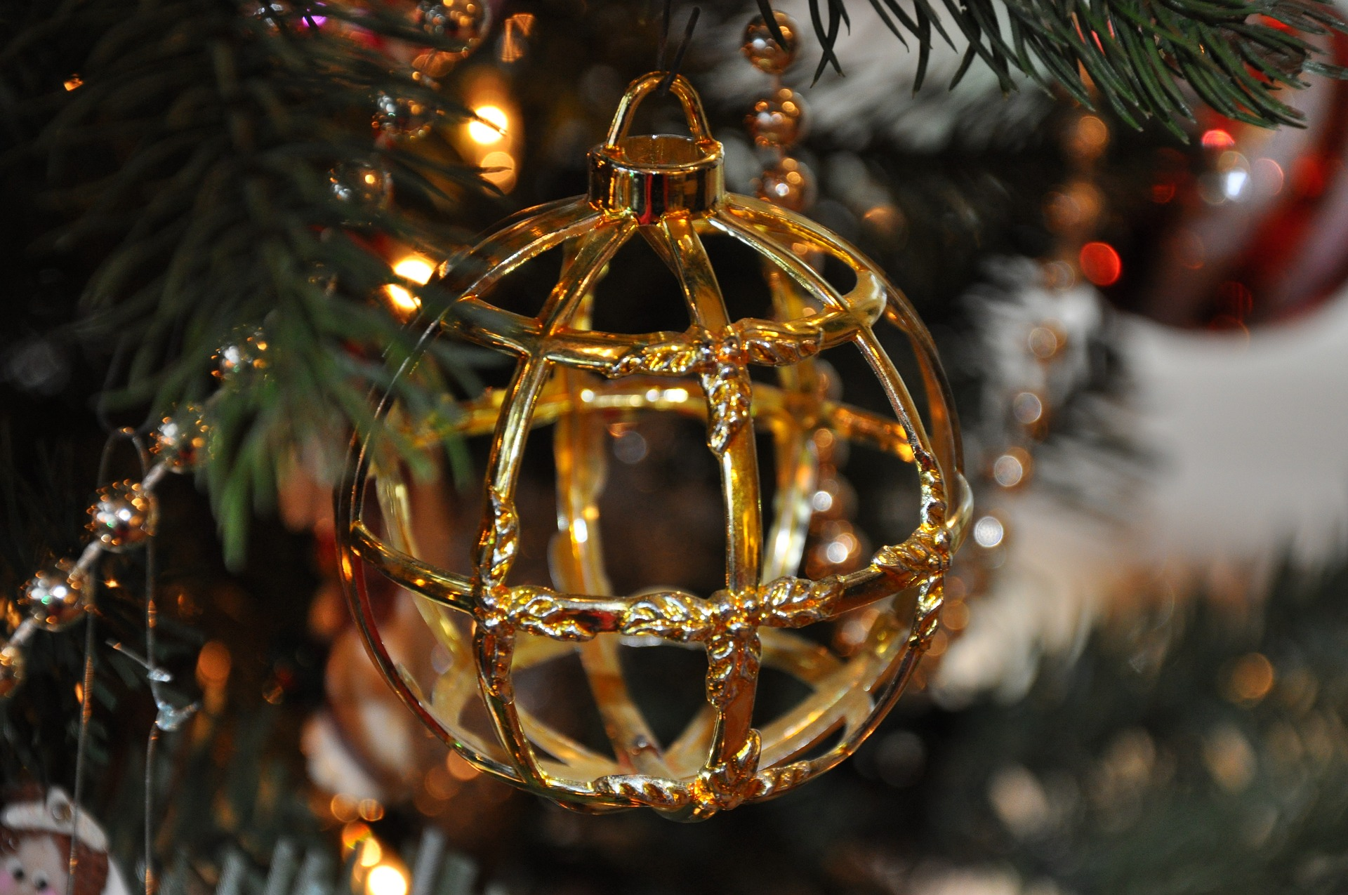 Old antique Christmas ornaments hanging on a Christmas tree.