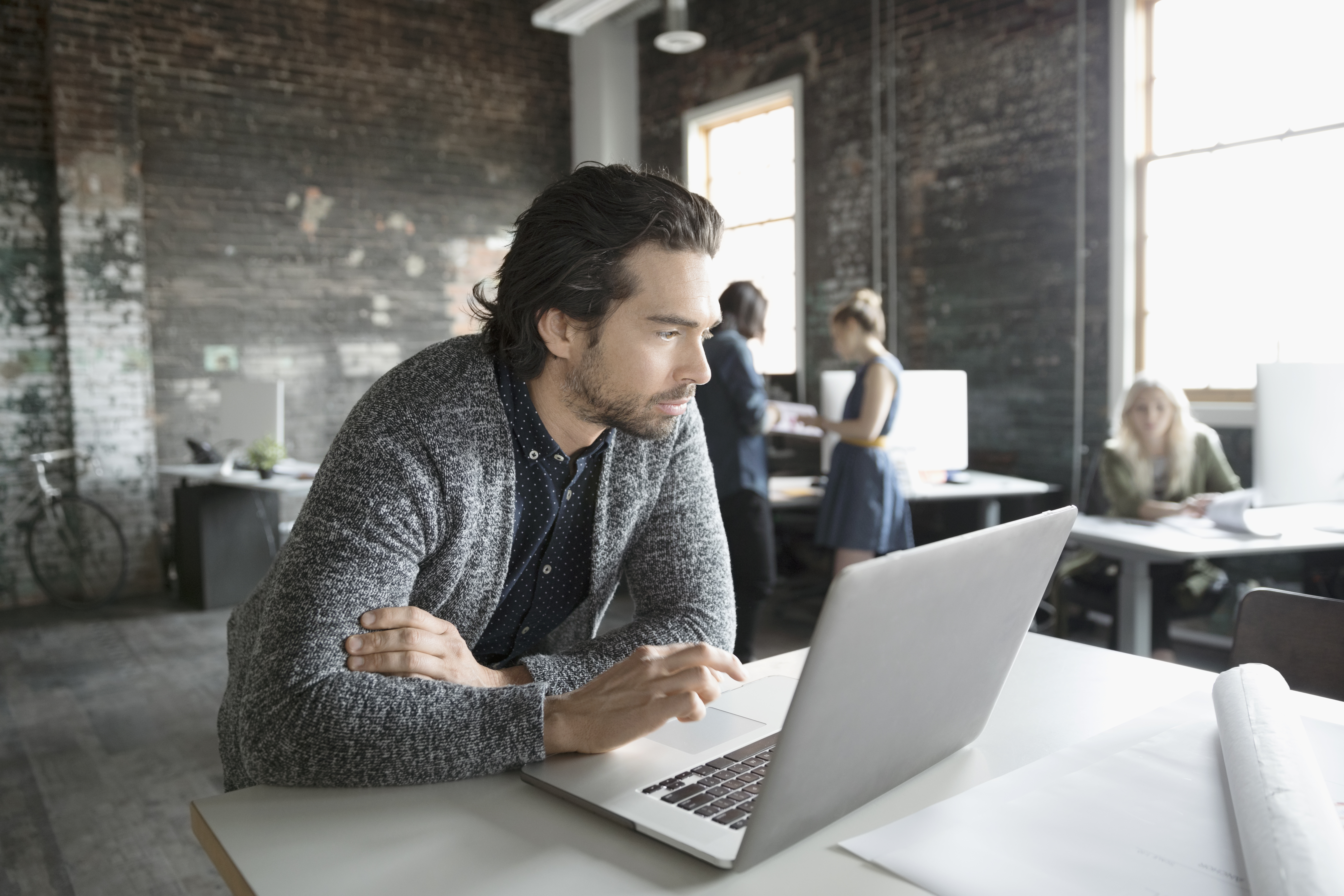 Man wearing a grey sweater working at a laptop in an office.