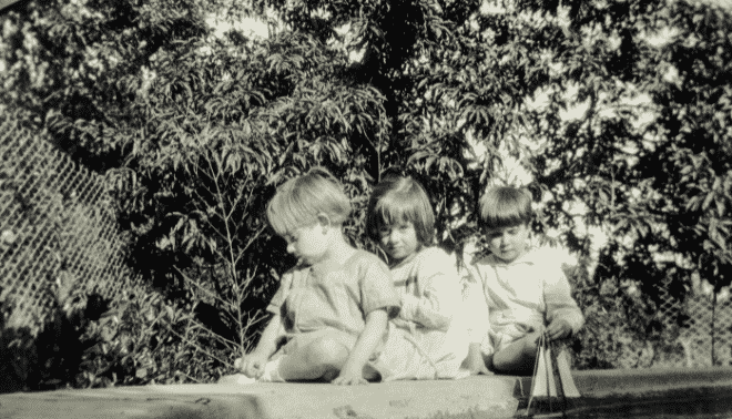 Vintage photo of three children sitting on a garden wall with a toy sailboat.