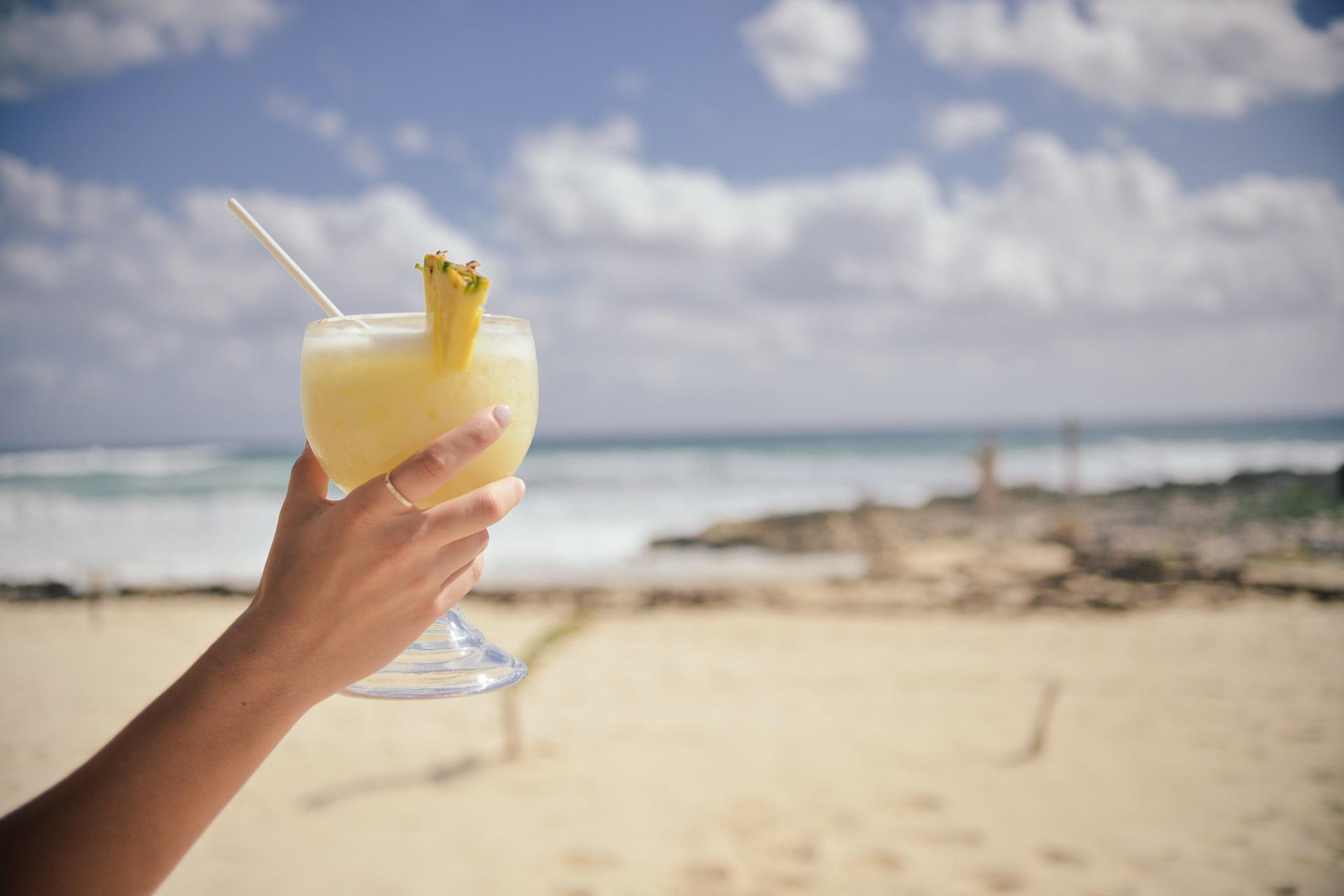 Woman holding a pina colada on a beach