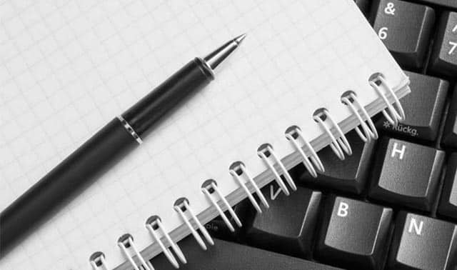 Notepad and pen resting on a keyboard.