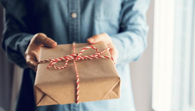 Man in a blue shirt holding a handmade gift.