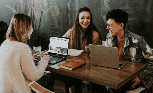 Three women sitting at a table in front of open laptop computers, creating a family history website together.