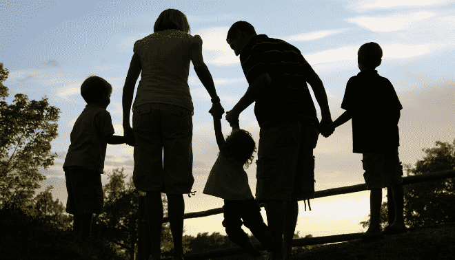 Family holding hands at sunset.