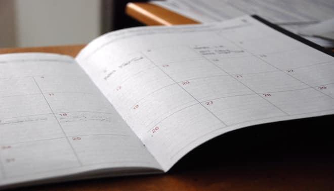 Calendar lying open on a wooden table.