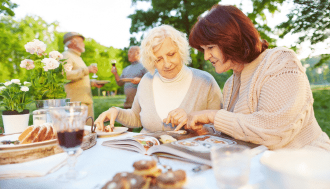 Two women at a picnic table looking at a family cookbook.