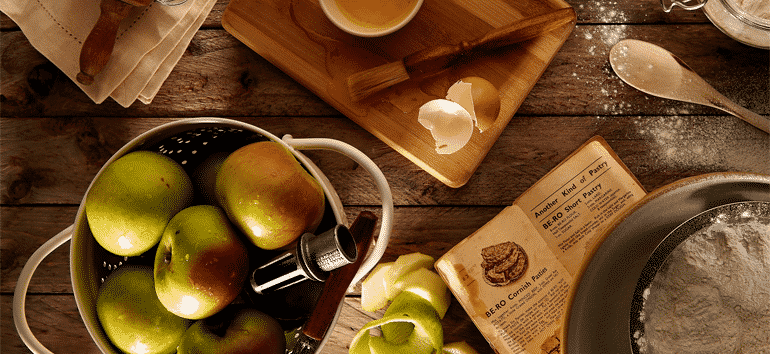 Apple pie ingredients on a messy kitchen table with a cookbook.