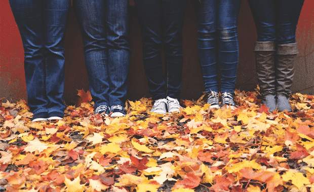 People standing in fall leaves.