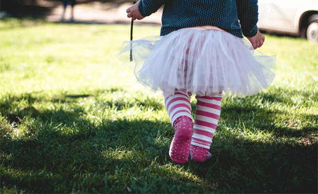 Young child taking small steps across a green lawn.