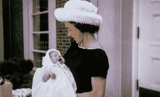 Woman in white hat and black dress holding a baby in white gown.