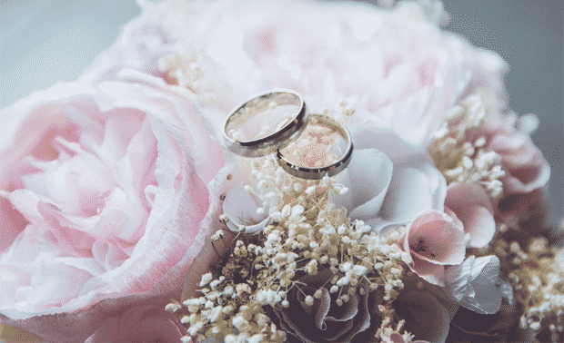 Two wedding rings laying on top of a bouquet of pink flowers.