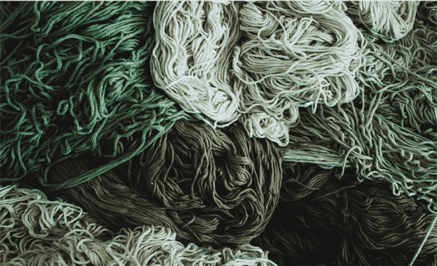 A tangled pile of green, white and brown yarn.
