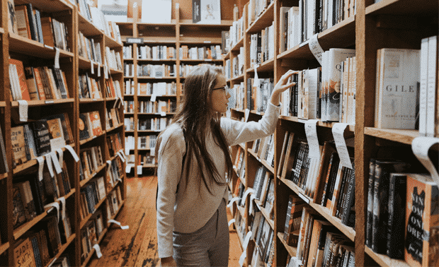 Woman standing in front of bookshelves, choosing a book to research unusual last names.