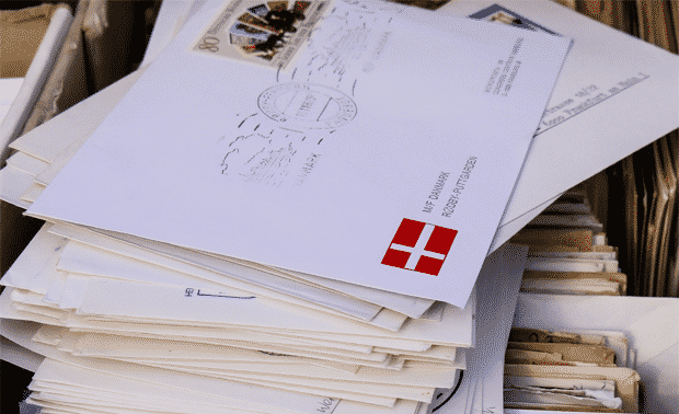 Pile of letters with Danish flag stamp.