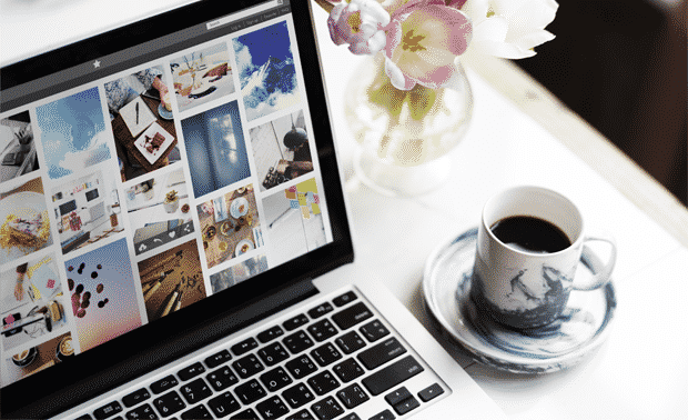 Open laptop computer showing organized photos next to a vase of flowers and coffee cup.