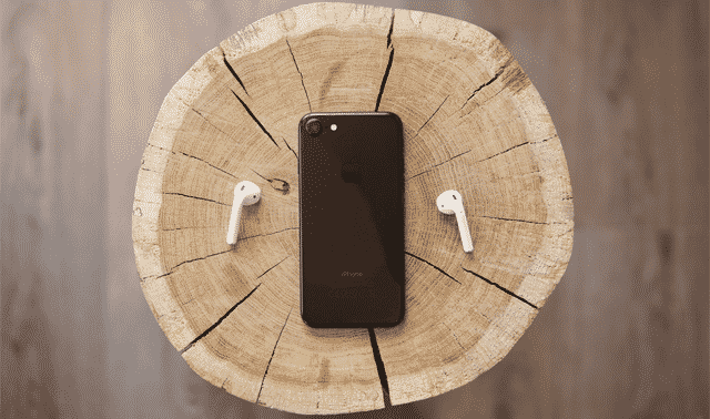 mobile phone on a tree stump with wireless headphones