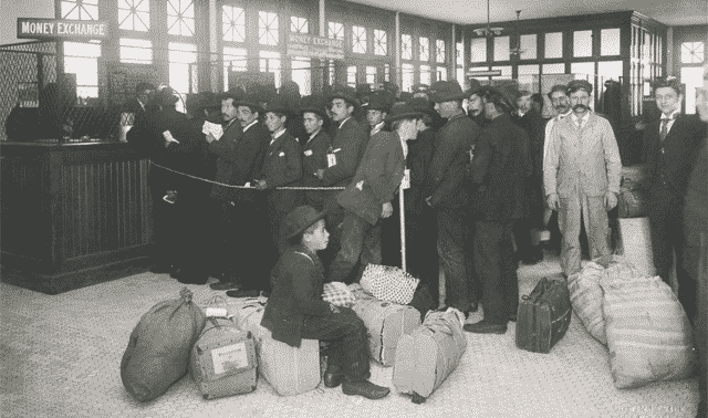 Ellis Island immigrants with baggage lined up at teller's windows marked money exchange.