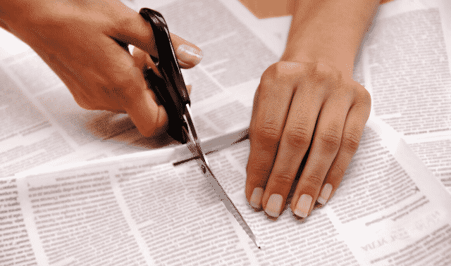 A person cutting out newspaper clippings with scissors.