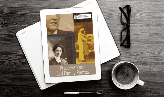 An iPad laying on top of an open book, showing the Preserve Your Family Photos ebook.