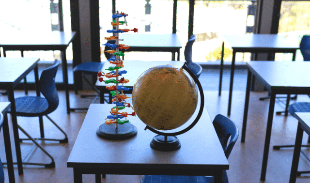 Globe and DNA model sitting on a desk in a sunny classroom.