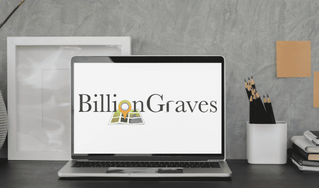 Laptop computer sitting on desk with BillionGraves.com on the screen.