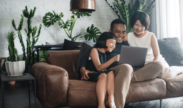 Family sitting on couch, looking at their family history website.