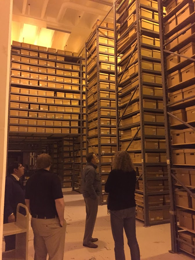 FamilySearch staff and local archivists survey tall shelves that contain several boxes of genealogy records at the Minnesota State Archives