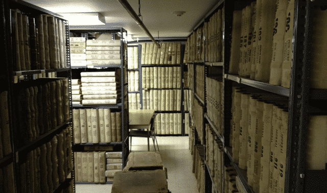 A dimly lit basement containing several binders of records on metal shelves