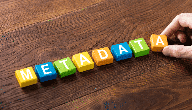 """The word """"metadata"""" spelled in colorful tiles on a wooden surface."""