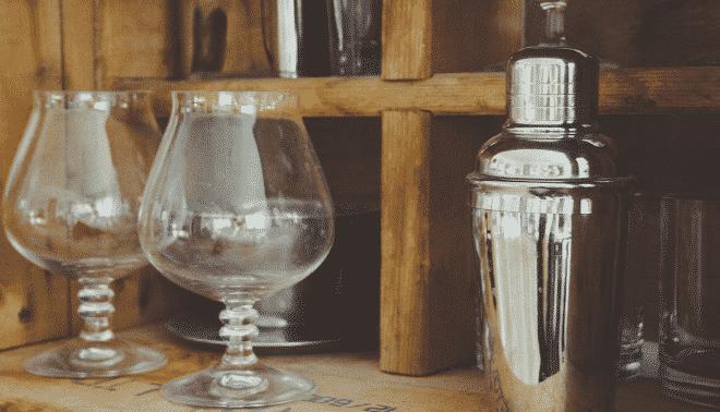 Vintage cocktail glasses on a wooden shelf.