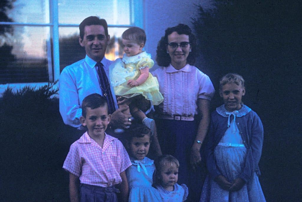 A photograph of a family standing together in front of a house in the 1950s whose color has become distorted over time, taking on a bluish tint