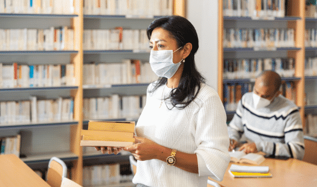 Woman wearing mask and holding books in library while searching genealogy records