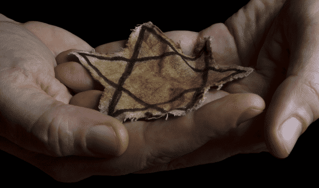 Pair of hands cradling a yellow fabric Star of David from the Jewish Holocaust
