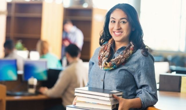 Woman using interlibrary loan system standing in library and holding stack of genealogy books