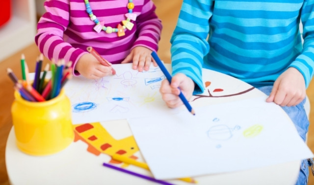 Two children sitting at school table and drawing