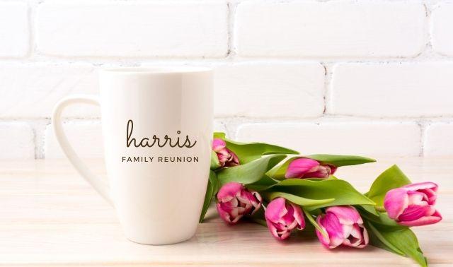 "White souvenir mug with ""Harris Family Reunion"" on it sitting next to pink tulips"