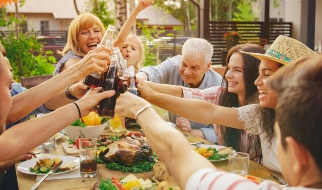 Group of people at a family reunion sitting around a table and toasting with soda bottles