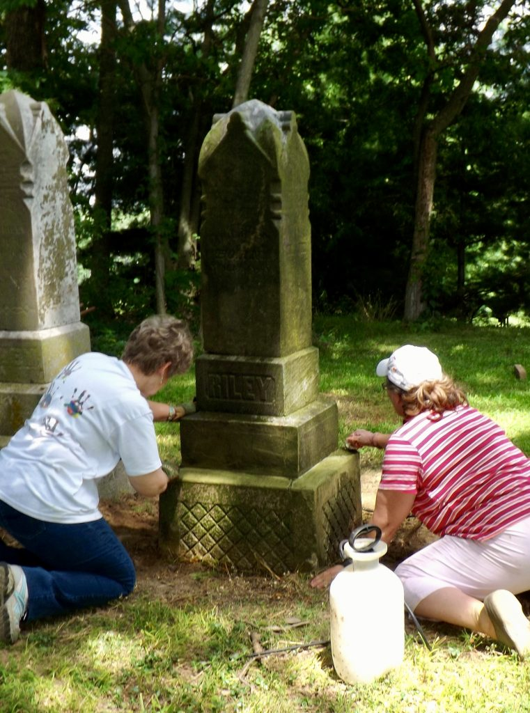 Two women cleaning a headstone.