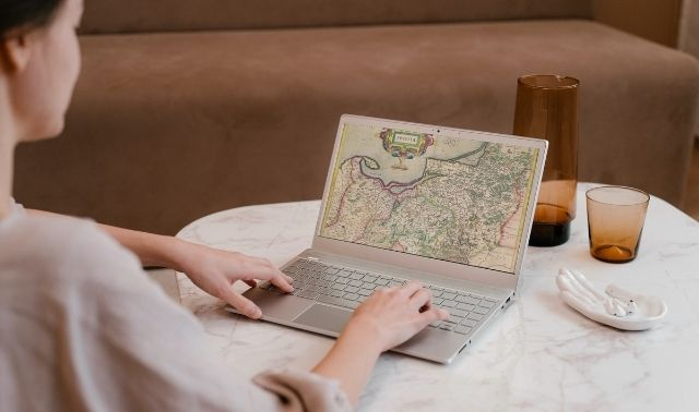 Woman sitting at laptop researching ancestors on map of Prussia